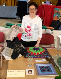 Brenda with samples of her work .